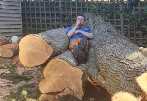 man laying on cut down tree